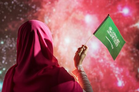 Muslim woman in a scarf holding flag of Saudi Arabia during fireworks at night.