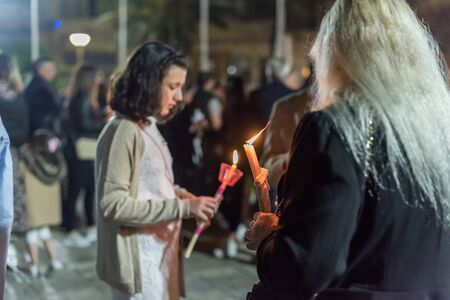 Heraklion, CRETE, GREECE - 28 APRIL 2019: People celebration with lit candles Easter night outside Agios Minas Cathedral