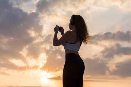 Silhouette young woman in the sport clothes, headphones and mobile phone  on the sunset sky backgrounds. The concept of healthy lifestyle