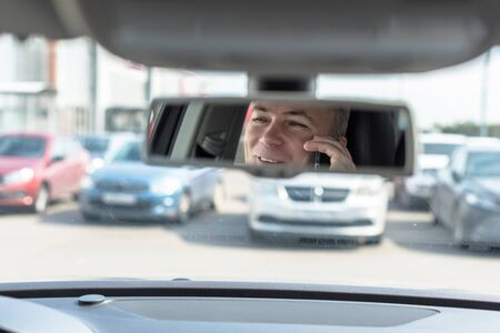Reflection of face of middle aged man talking on a mobile phone and laughing in the car rear view mirror.