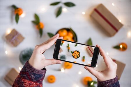 Woman blogger taking a picture on mobile phone her decoration of mandarin, Christmas tree, gifts, luminous garland on the white wooden boards background