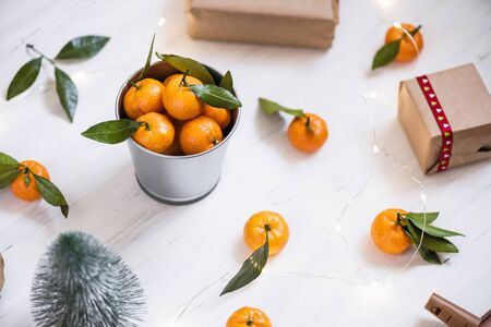 Christmas decoration of mandarin in an iron small bucket, Christmas tree, gifts and a luminous garland on the white wooden boards background