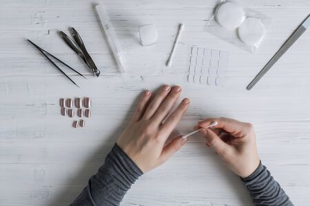The process of putting artificial (fake) fingernail on the finger. Woman manicure. Flat lay.