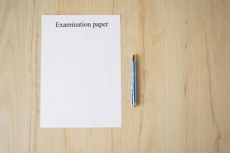 Empty examination paper for university with pen on the school desk. Copyspace. Mockup. Flat lay