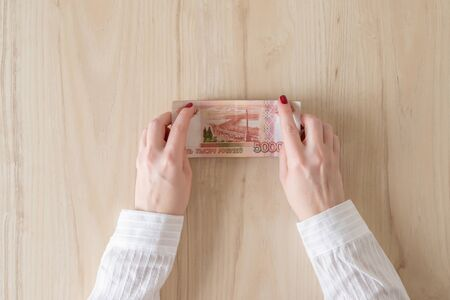 woman hold banknote five thousand rubles in hand and count it. Money exchange. Bank operation. Finance services. Financial market. Foreign currency exchange point. Concept. Flat lay