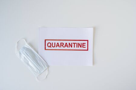 The word quarantine on a sheet of paper lying on an office desk. Worldwide pandemic concept, production and work shutdown
