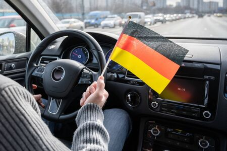 Middle aged man with Germany, flag driving a car.  Europe. Foto de archivo
