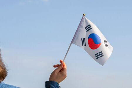 Woman hand with South Korea swaying flag on the blue sky. Concept