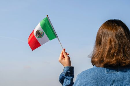 Woman hand with Mexico swaying flag on the blue sky. North America. Concept Фото со стока