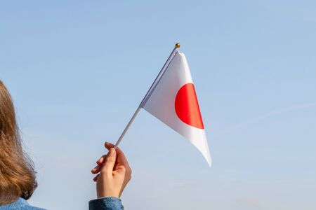 Woman hand with Japanese swaying flag on the blue sky. Japan. Concept
