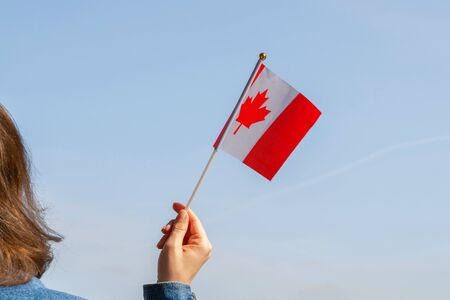Woman hand with Canada swaying flag on the blue sky. America. USA. Concept Фото со стока