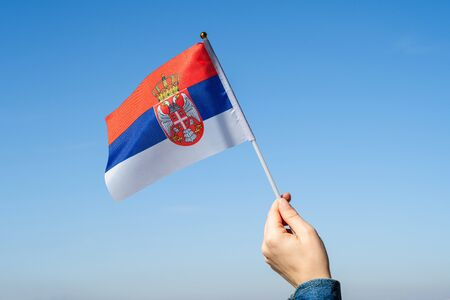 Woman hand with Serbian swaying flag on the blue sky. Serbia. Concept