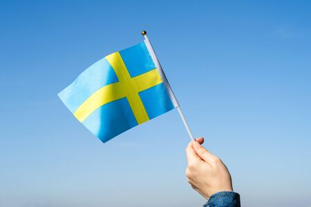 Woman hand with Swedish swaying flag on the blue sky. Sweden. Concept