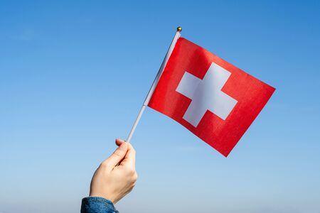 Woman hand with Swiss swaying flag on the blue sky. Switzerland. Concept