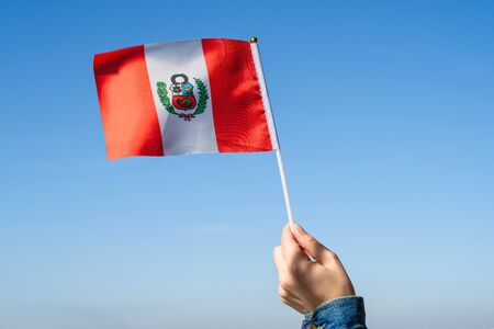 Woman hand with Peru swaying flag on the blue sky. South America. Concept