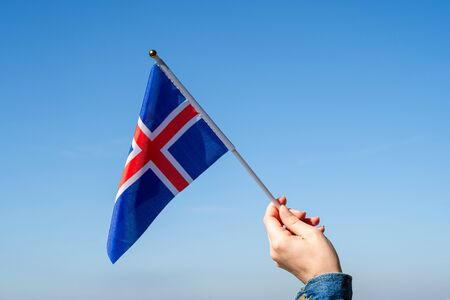 Woman hand with Iceland swaying flag on the blue sky. Concept