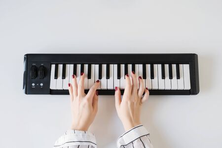 Woman hand playing on a home synthesizer on a white table. Piano keyboard. Flat lay. Foto de archivo