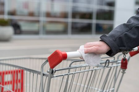 Man cleaning handle of shopping cart, trolley using antivirus antibacterial wet wipe (napkin) for protect himself from bacteria and virus. grocery store, supermarket Reklamní fotografie