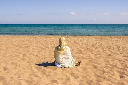 Back view of lonely Muslim woman traveler in a colorful headscarf, scarf sitting on the sand on the beach and looking on the sea. Standard-Bild