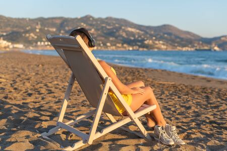 Relaxed woman sitting on a sunbed wearing headphones meditating listening to music on the beach at sunset or sunrise. Girl in the yellow summer suit, sand, looking on the sea.