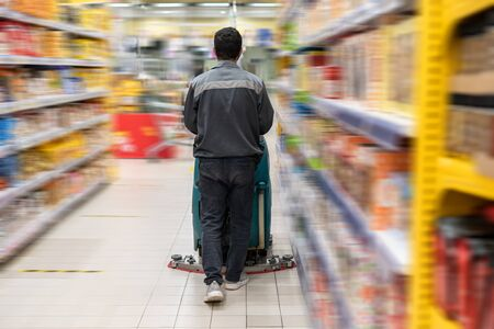 Floor care and cleaning services with washing machine between racks and shelves with product of a grocery store. disinfection and sanitization in supermarket. In a motion.
