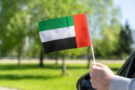 Man holding United Arab Emirates (UAE)  flag from the open car window. Concept