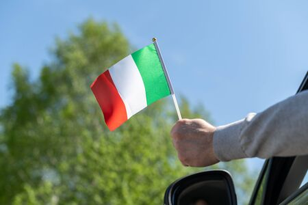 Man holding Italy flag from the open car window. Concept