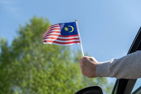 Man holding Malaysia flag from the open car window. Concept