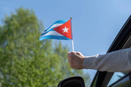 Man holding Cuba flag from the open car window. Concept 免版税图像