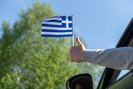 Man holding Greece flag from the open car window. Concept