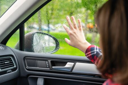 Back view of lonely girl touching by hand rainy window with drop of car.