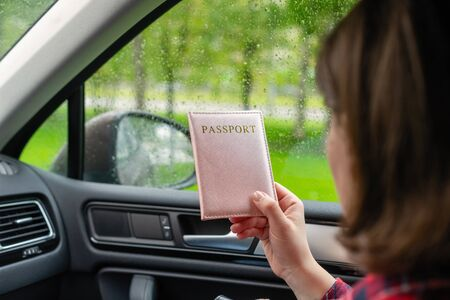 Passenger girl holding passport sitting in car for check customs officers. Border control concept. Travel