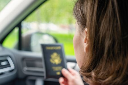 Passenger girl holding passport of America (USA) sitting in car for check customs officers. Border control concept. Travel  Stok Fotoğraf