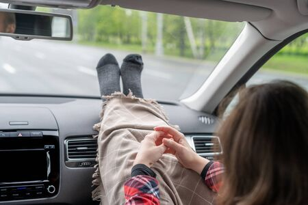 Woman passenger legs in socks wrapped in a plaid on car dashboard while travel on the highway. Freedom concept.