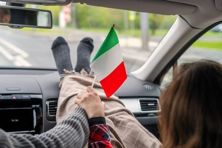 Woman passenger and man driver with flag of Italy traveling on the highway by car. Couple on a trip. Freedom concept.