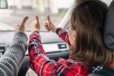 Woman passenger, man showing thumbs up traveling by car on the highway . Freedom  concept.
