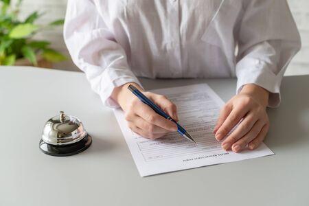 Woman filling hotel reservation form. Silver vintage bell on reception desk. Hotel service, registration.