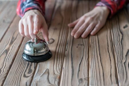 Hand of guest ringing in silver bell. on wooden rustic reception desk with copy space. Hotel, restaurant service. Selective focus
