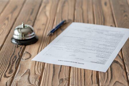 Hotel reservation form and silver vintage bell on wooden rustic reception desk. Hotel service, registration. Selective focus