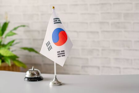 Silver vintage bell with national flag of South Korea on reception desk with copy space. Hotel service. Travel, tourism. Selective focus. Asia, Concept.