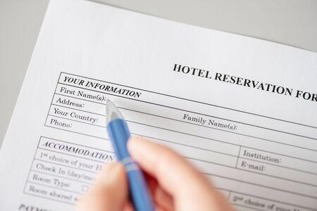Woman filling hotel reservation form. reception desk. Hotel service, registration.