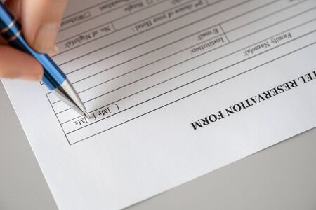 Woman filling hotel reservation form putting check mark on Mrs. Reception desk. Hotel service, registration. Close up. Selective focus.