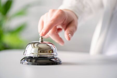 Main d'invité sonnant en cloche d'argent. bureau d'accueil avec espace copie. Service hôtelier. Mise au point sélective