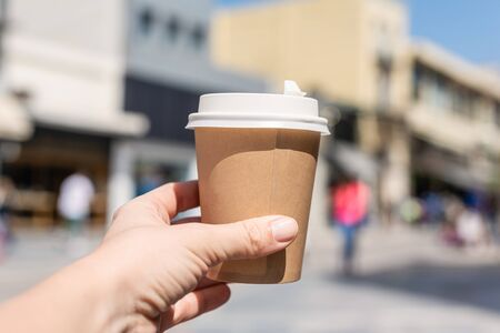 Girl with paper cup of coffee on a street. Coffee take away. Selective focus