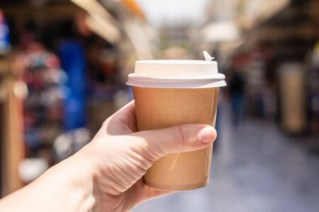 Girl with paper cup of coffee on a street. Coffee take away. Selective focus Stok Fotoğraf - 148183465