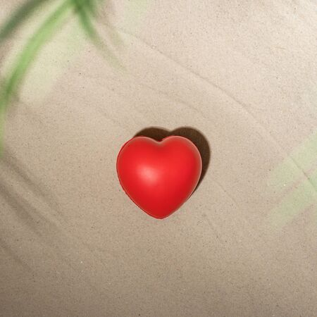 Red heart on sandy tropical beach under branches of palm and shadow palm tree. Valentines day, love. Holiday concept. Creative, background, travel, summer.