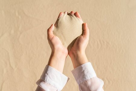 Female hand with a handful of sand. Beach holiday concept. Creative, background, copy space, travel, summer. Flat lay