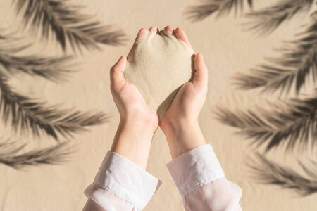 Female hand with a handful of sand among shadow of a palm tree branch of a sandy tropical beach. Holiday concept. Creative, background, copy space, travel, summer. Flat lay