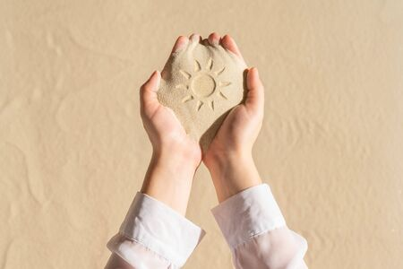 Female hand with a handful of sand with sun hand-drawn on sandy tropical beach. Holiday concept. Creative, background, travel, summer. Flat lay Banco de Imagens