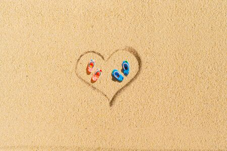 Aerial view of two pair of flip flops in shape of heart on sandy tropical beach. Valentines day. Holiday concept. Creative, background, travel, summer. Flat lay